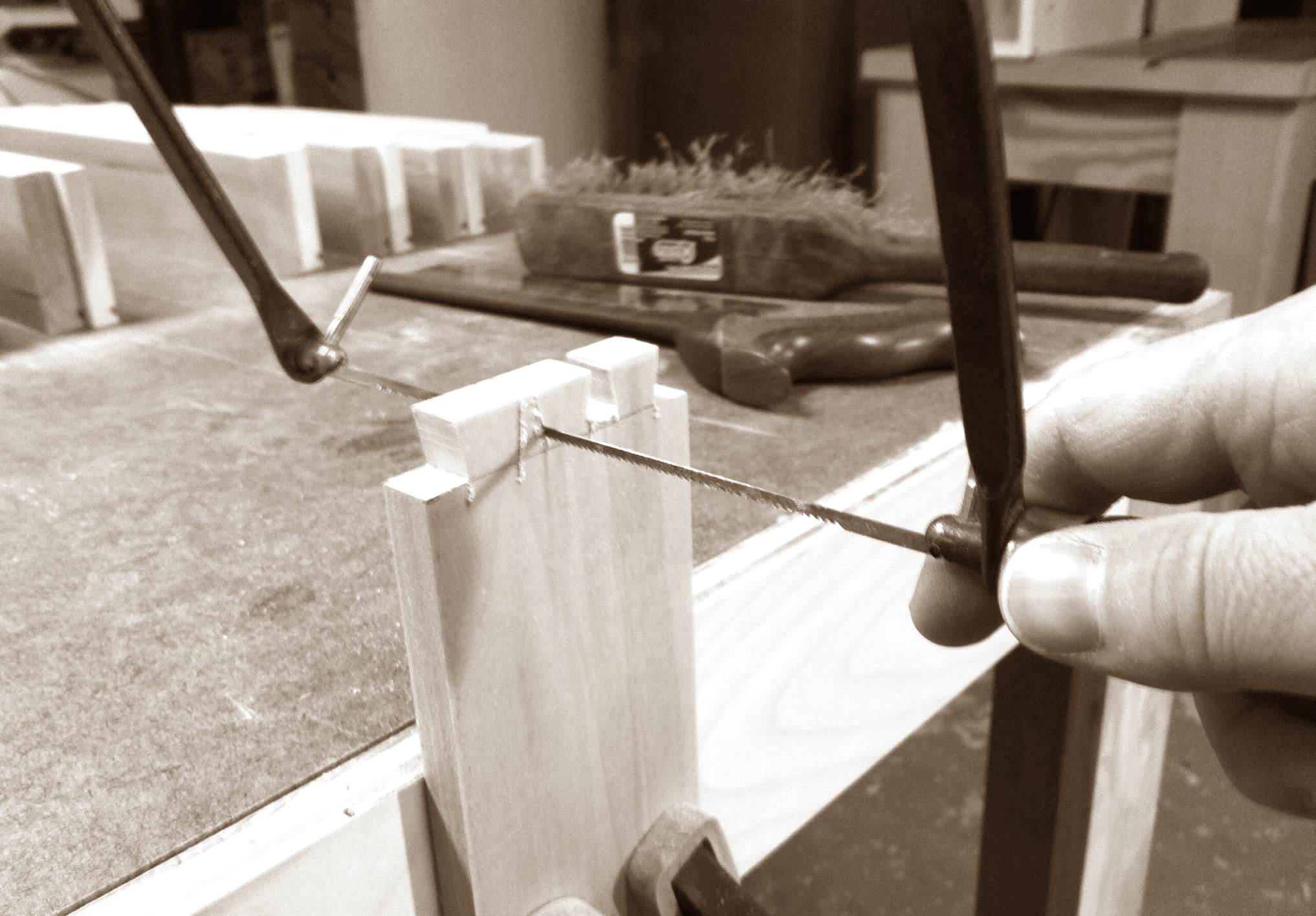 Using coping saw to cut waste between tails, staying just off the lines