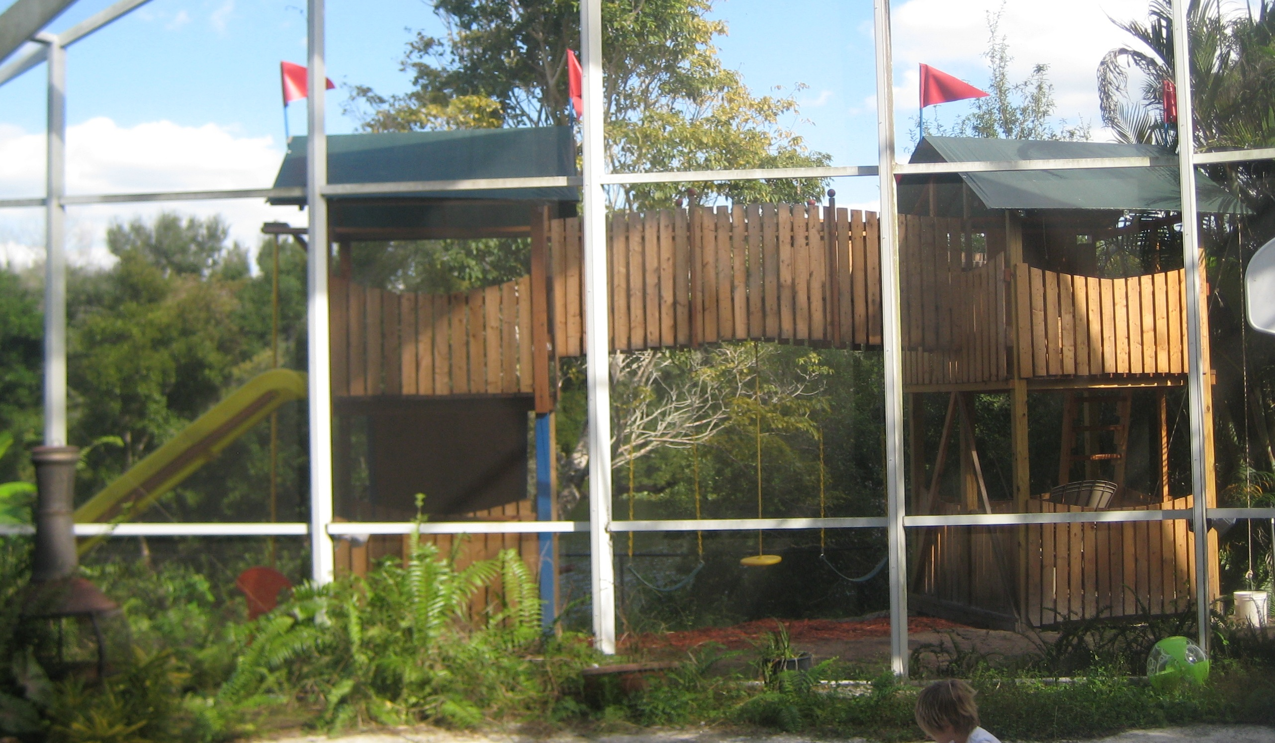 Liam's playset as completed, viewed from inside the backyard arboretum