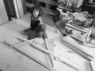 Lucas working on his woodworking project on the floor of the shop